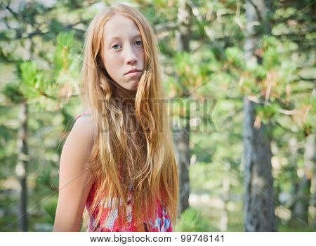 Portrait of young redhead girl, outdoot shot in forest