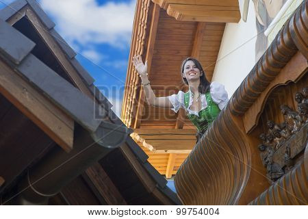 Woman In Dirndl Standing On Balcony