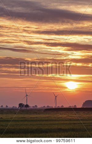 Two wind turbines at northern german marsh landscape in sunset