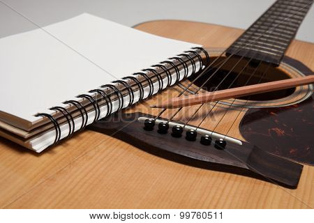 A Notebook and pencil on a guitar