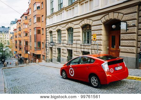 Red color Toyota Prius car parked at sidewalk on the David Bagar