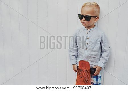 Serious Trendy Little Boy Posing With A Skateboard