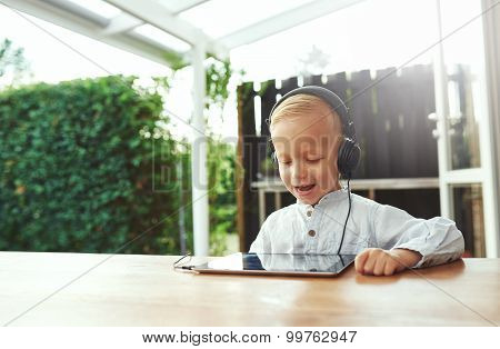 Happy Vivacious Little Boy Listening To Music