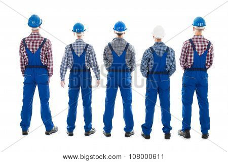 Rear View Of Male Carpenters Standing In Row