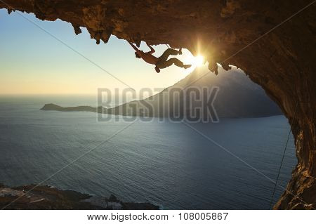 Male rock climber climbing along a roof in a cave at sunset, Kalymnos island, Greece. poster