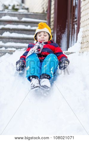Happy Child In Colorful Clothes Having Fun With Riding On Snow,