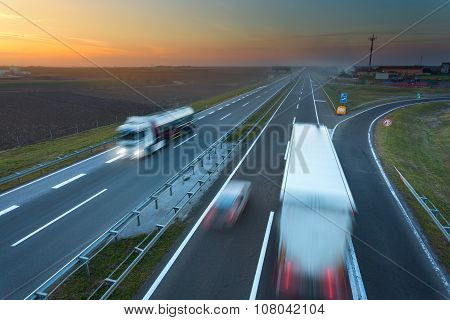 Many Trucks In Motion Blur On The Motorway At Sunset