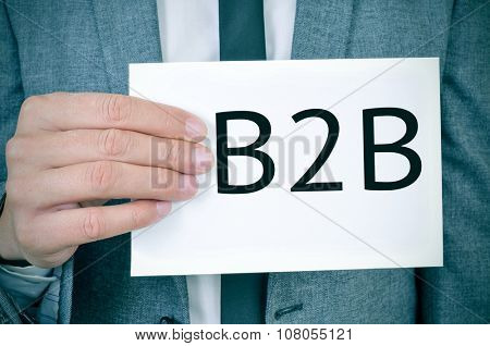 closeup of a young caucasian man in a grey suit showing a signboard with the word B2B written in it