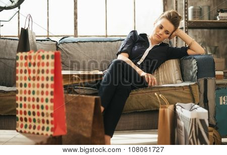 Tired Brunet Woman Sitting On Couch Among Shopping Bags In Loft