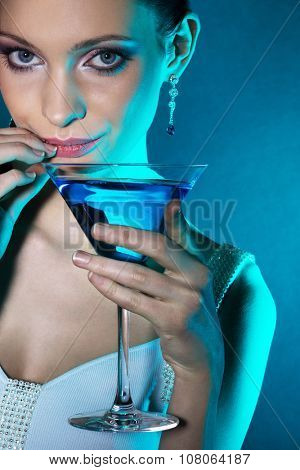 Young woman with martini glass in blue light. Focus on eyes.