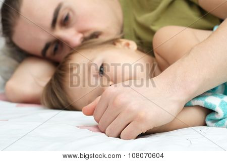 Daddy holding ailing baby hands lying together poster