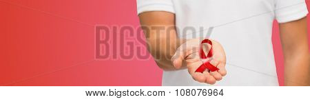 medicine, health care, charity and people concept - close up of male hand holding red hiv aids or heart disease awareness ribbon