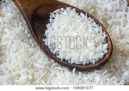 Grated Coconut Flakes With A Wooden Spoon