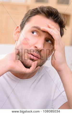Beaten man touching his face