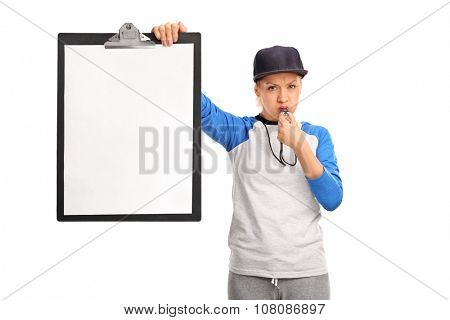 Angry female sports coach holding a clipboard with a blank paper on it and blowing a whistle isolated on white background