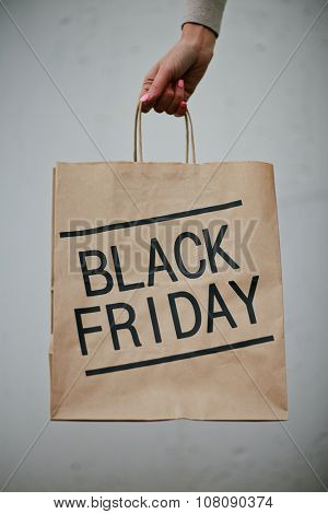 Paperbag announcing Black Friday held by human hand