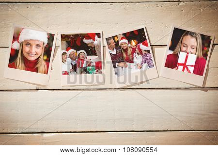 Instant photos on wooden floor against festive blonde smiling in santa hat