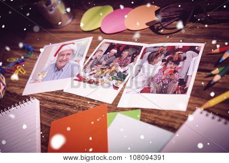 High angle view of office supplies and blank instant photos against smiling mature man in santa hat toasting with white wine