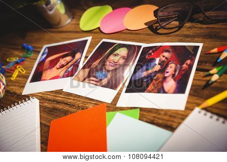 High angle view of office supplies and blank instant photos against pretty brunette dancing and smiling