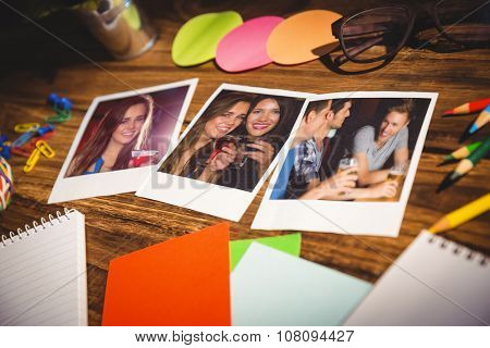 High angle view of office supplies and blank instant photos against pretty girl drinking a cocktail