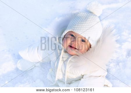 Cute Little Baby In A White Jacket And White Hat Sitting In Fresh Winter Snow