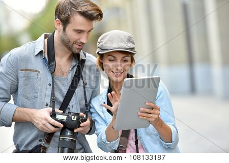 Team of photographers checking shots on digital tablet