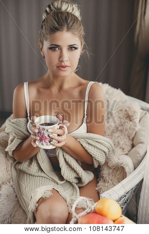 Portrait of a model sitting in a chair with a cup of tea in his hands