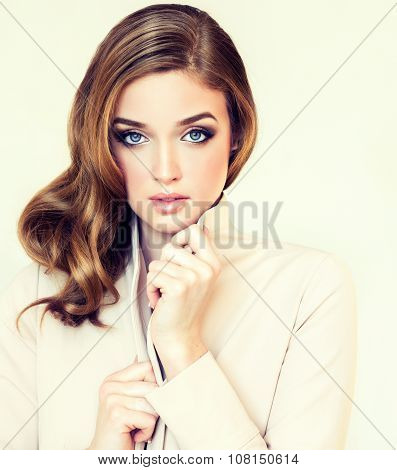 Beautiful girl model in beige jacket with a stylish hairstyle curly hair on the side