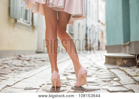 Woman wearing nude colored shoes and skirt