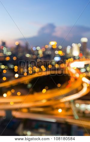 Blurred bokeh light during twilight, city intersection highway with office building background