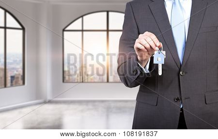 A Man In Formal Suit Holds A Key In A Modern Loft Panoramic Apartment Or Office. Rent Or Buy New Hom