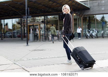 Smiling young woman traveling with a wheeled suitcase