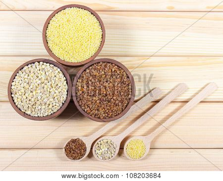 Pearl barley buckwheat and millet groats on wooden background. poster