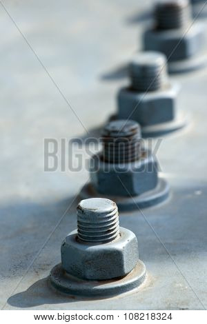 Screw and bolts on a massive girder gray bridge. Original background.