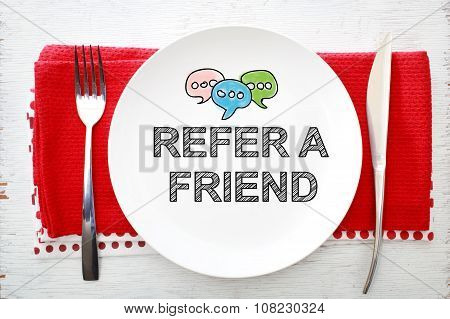 Reffer A Friend Concept On White Plate With Fork And Knife