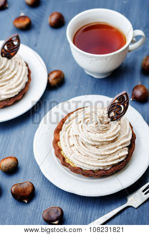chocolate tartlet with chestnut cream frosting on wooden background poster