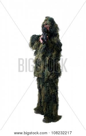 A well armed man wears a Ghilly Camouflage Moss style suit to stay hidden from the enemy or prying eyes while hiding in the woods. Ghilly Suits are used by Snipers and Hunters to blend into the woods