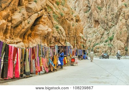 TINERHIR, MOROCCO, APRIL 11, 2015: Local sellers and their stands with souvenirs and fastfood on shore of Todgha river in Todgha Gorge