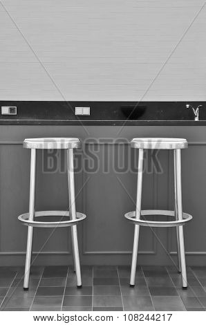 Two Bar Chairs In Front Of A Bar