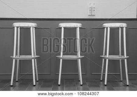 Three Bar Chairs In Front Of A Bar