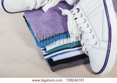 Fashion Ideas And Concepts. Pair Of White Fasionable Sneakers Close To Stack Of Prepared Clothing.