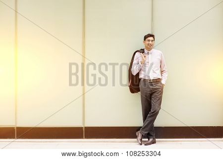 Portrait of fullbody Asian Indian business man smiling and standing outside modern office building block.