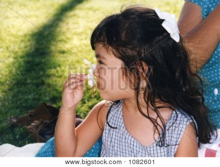 Pretty Girl Smelling A Flower