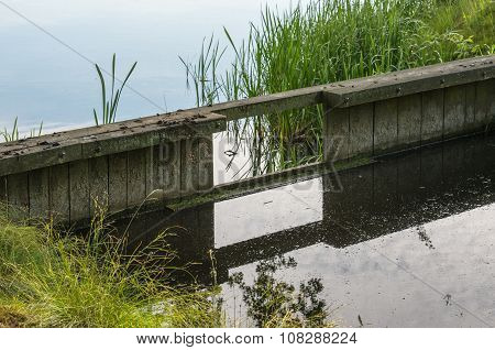 Wooden Weir Reflected In A Ditch