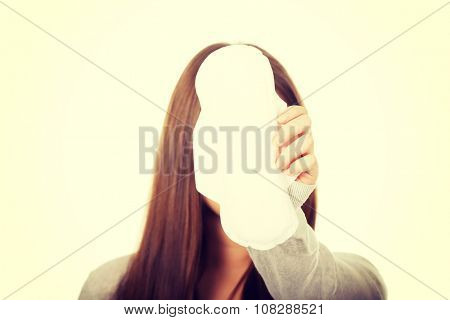 Tren woman with menstruation pad covering face.