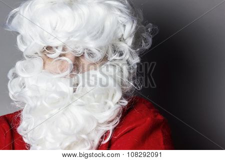 Portrait Of Santa Claus With Tousled Hair And Beard In Front Of Grey Background