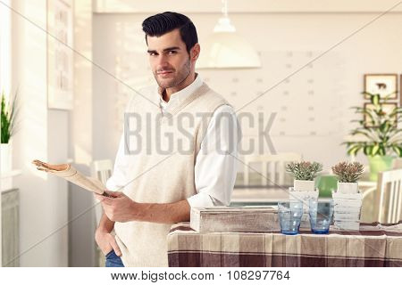 Handsome casual caucasian man at vintage italian home with newspaper in hand. Wearing sleeveless sweater, standing at dining room, looking at camera, smiling, bristly.