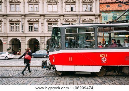 People cross the tram tracks on the street Malostranske namesti