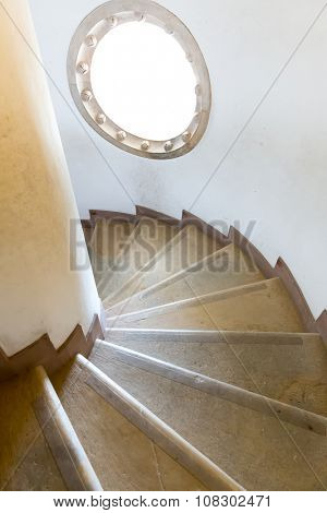 Spiral wooden stairs with a little round window