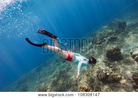 Underwater photo of woman snorkeling and free diving in a clear tropical water at coral reef with giant clams